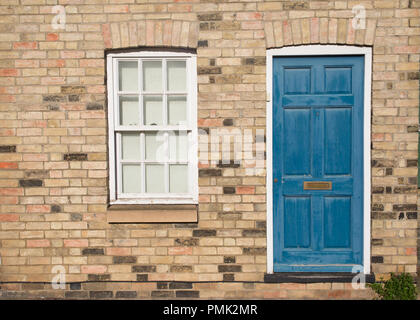 Blue vintage front door on a restored brick wall of a Georgian house residential building with white wooden sash window - Stock Image