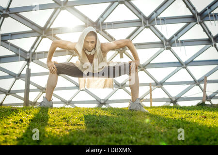 Attractive athletic man practicing yoga and warming up outdoors in modern park. - Stock Image