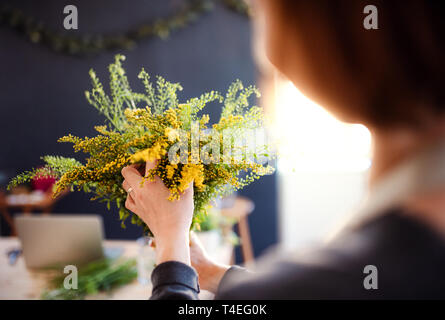 A midsection of young creative woman arranging flowers in a flower shop. A startup of florist business. Rear view. - Stock Image