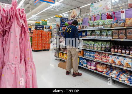 Inside a Walmart store with male employee stocking a shelf. USA. - Stock Image