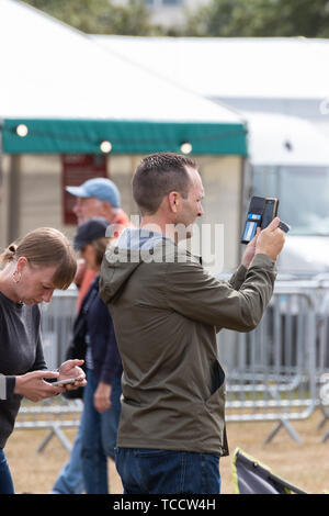 A man using a mobile phone or cell phone to take a photo at an outdoor event - Stock Image
