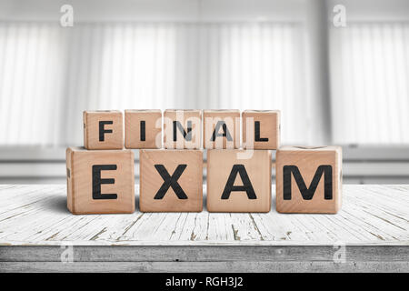 Final exam sign in a bright education room on a wooden table - Stock Image