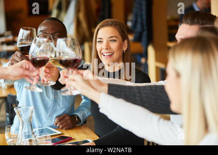 Group of young people celebrates birthday in the restaurant and toast with glass of wine - Stock Image