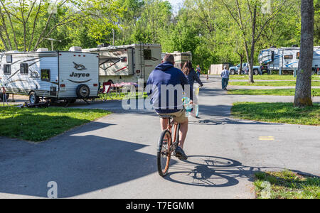 LIMESTONE, TN, USA-4/26/19:  A man and woman ride bicycles through an RV park on a sunny, spring day. - Stock Image