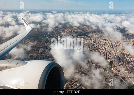 view showing the jet engine and wing tip of a ryanair passenger Boeing 737 jet flying above the clouds with city below - Stock Image