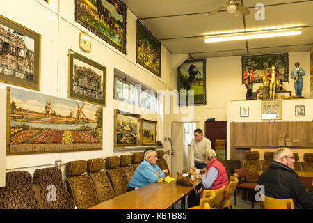 Interior of the Amersham Fair Organ Museum on an open day, Buckinghamshire, UK, with people sitting in the café area with tapestries and pictures - Stock Image