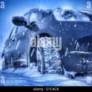 Smal car plouging through the snow. - Stock Image