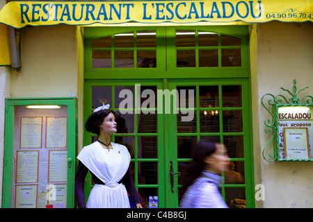 Arles; Bouches du Rhone, France; A young woman walking in front of a restaurant - Stock Image
