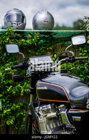 Black motorcycle Kawasaki Z 1300 with two grey motorcycle helmets in the background. - Stock Image