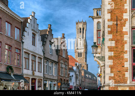 Typical Bruges architecture and shop fronts featuring chocolate and lace shops, the 83-metre high Belfry in the - Stock Image