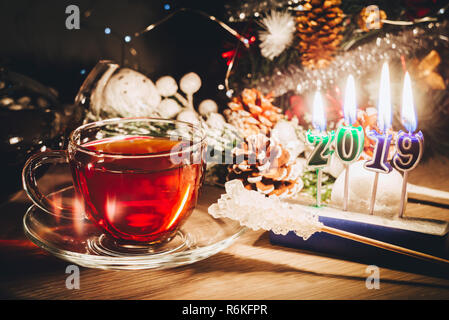 2019 year is coming. Nice candles burning near Christmas tree and cup of tea. Happy New Year - Stock Image