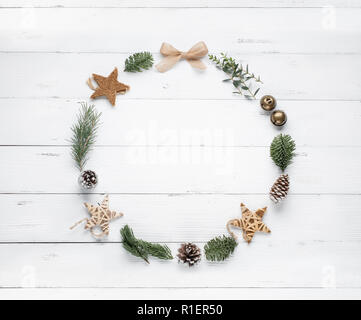Christmas wreath made of fir branches, balls and pine cones on wooden background. Flat lay - Stock Image