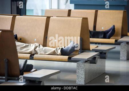 Men sleeping at airport, Incheon International Airport, South Korea - Stock Image