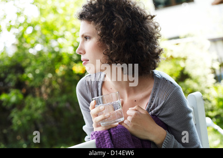 portrait of young woman in garden with glass of water - Stock Image
