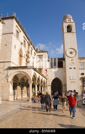 Tourists and visitors stroll outside the Sponza Palace and Belltower in the walled city of Dubrovnik in summer sunshine - Stock Image