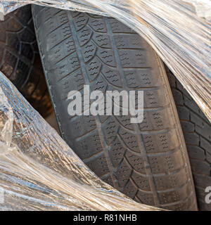 Worn out tires of heavy vehicles wrapped in plastic - Stock Image