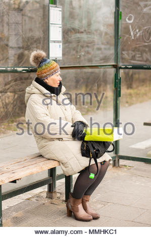 Oder woman sitting on a bench of a public transport stop waiting for the bus in Poznan, Poland - Stock Image