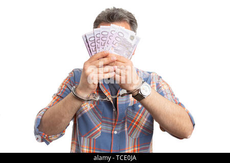 Corrupted man covering face with money bills and handcuffed hands as bribe concept isolated on white background closeup - Stock Image