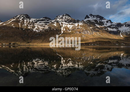 Spring snow mountain reflection in Skjelfjord, Flakstadøy, Lofoten Islands, Norway - Stock Image
