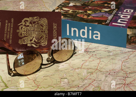 UK Passport, India guide book and sunglasses on a map of India - Stock Image