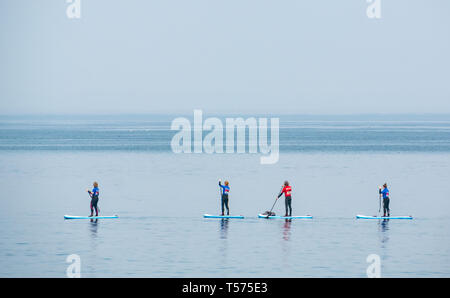 Dunbar, East Lothian, Scotland, UK. 21st Apr 2019. UK Weather:  People enjoy the very sunny hot Easter day weather at Eye Cave cove. A group of paddle boarders in very calm sea for a lesson with Coast to Coast surf school - Stock Image