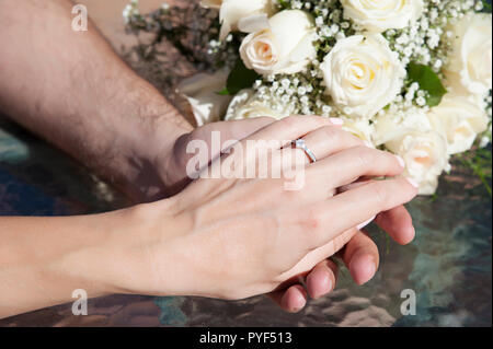 Caucasian female and male, delicately holding hands, with visible engagement ring on the woman's finger, and with an ivory roses wedding bouquet - Stock Image