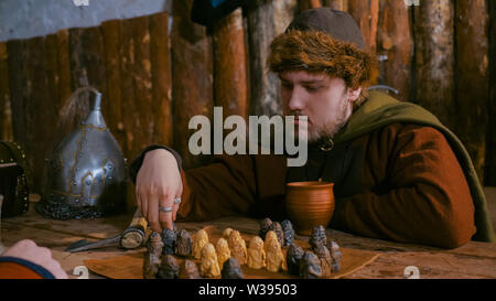 Portrait of man in russian ethnic suit playing chess - Stock Image