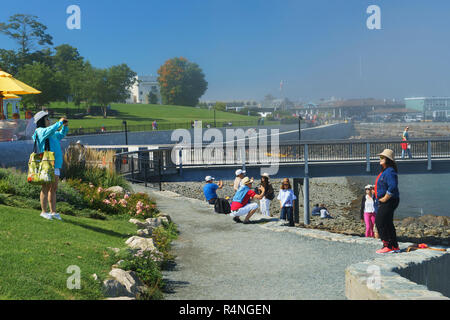 Asian tourists taking pictures in front of Frenchman Bay, Bar Harbor, Maine, USA. - Stock Image