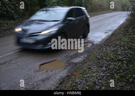 Car seeking to avoid a pothole on the side of the road in the north Oxfordshire village of Hook Norton - Stock Image