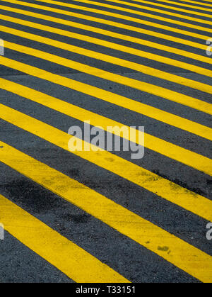 yellow stripes painted on a road. - Stock Image