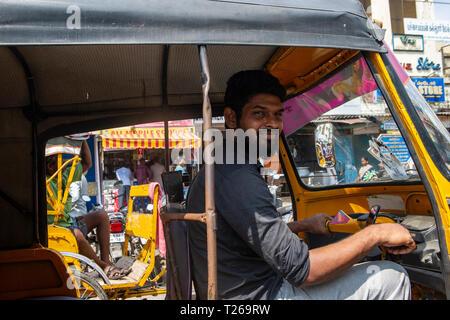 A tuk tuk driver smiles to camera in bustling Chennai, India - Stock Image