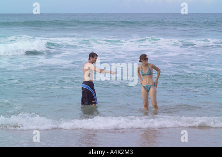 Young couple playing in the surf at a Puerto Rican beach. - Stock Image