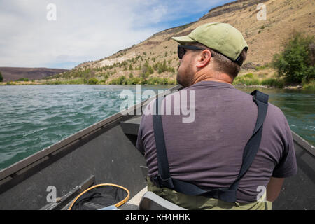 Fly fisherman sitting in a drift boat while floating the river to get to the next fishing access on the Lower Deschutes River near Warm Springs Oregon - Stock Image