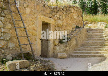 A retro style stone house in the open air museum of Nazareth Village Israel. houses in the modern Nazareth can be seen in the background. This site gi - Stock Image