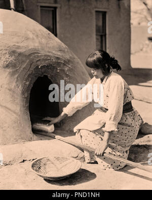 1930s NATIVE AMERICAN WOMAN BAKING BREAD KIVA OVEN SAN ILDEFONSO PUEBLO MEW MEXICO USA - i1562 HAR001 HARS UNITED STATES OF AMERICA CARING B&W NORTH AMERICA NORTH AMERICAN LOAF MEXICO HIGH ANGLE TRADITION NATIVE AMERICAN PUEBLO NATIVE AMERICANS YOUNG ADULT WOMAN BLACK AND WHITE HAR001 ILDEFONSO INDIGENOUS KIVA OLD FASHIONED - Stock Image
