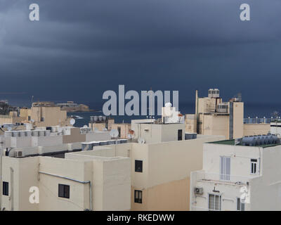 Storm clouds over the roofs of apartment blocks in Saint Julians Malta - Stock Image