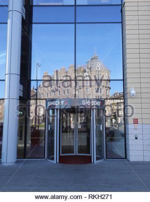 Malmaison hotel reflected in Sleeperz hotel entrance Dundee Scotland  January 2019 - Stock Image