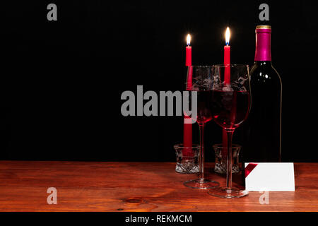 Beautiful etched wine glasses and bottle of red wine, red candles, on wooden table with name tag on dark background. Valentines, Mothers Day, Easter,  - Stock Image