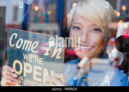 Portrait confident young female shop owner holding Open sign at window - Stock Image