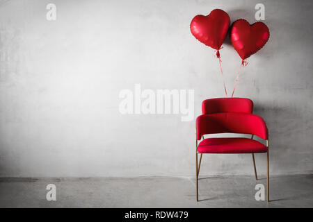 Red chair with heart shaped balloons floating on concrete wall  background. - Stock Image