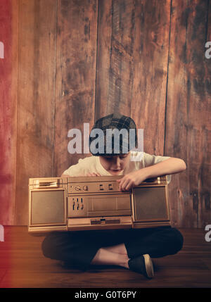 A child is listening to a gold stereo vintage music boombox with a wood background for a entertainment or audio - Stock Image
