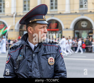 Policeman controlling crowd at St Petersburg City Day Parade, Nevsky Prospekt, St Petersburg, Russia - Stock Image