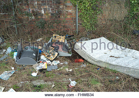 Discarded television set and a mattress, amongst other rubbish, dumped on side of road. Newport, Gwent, Wales, UK. - Stock Image