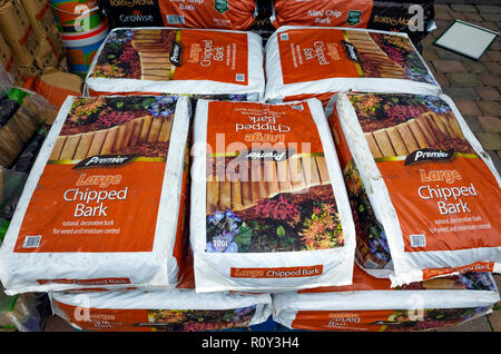 A stack of bags of Premier Large Chipped Bark in a garden centre, for dressing plant beds to retain moisture and discourage weeds. - Stock Image