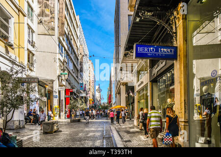 Tourists and local Greeks sightsee and shop along Ernou Street, the main shopping street in Athens, Greece. - Stock Image