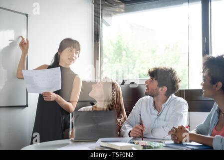 Businesswoman giving presentation in office - Stock Image