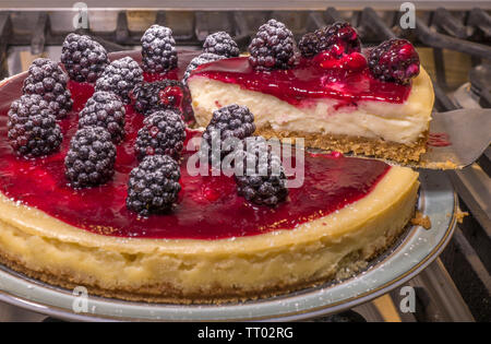 A triangular slice being lifted from a whole, circular cheesecake, with blackberries in coulis on top, fresh from the oven and resting on a plate. - Stock Image