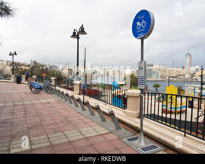 Seaside promenade in Sliema Malta with parking space for rental bikes and a children's playground - Stock Image