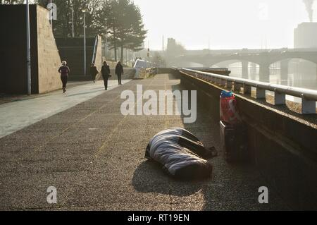 Glasgow, UK, 27th February 2019 : Homeless person sleeping rough for a number of nights now under the South Portland Suspension Bridge,with commuters walking past every morning. Credit: Pawel Pietraszewski / Alamy Live News - Stock Image