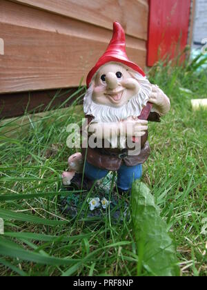 Garden gnome standing on the grass in a garden. - Stock Image